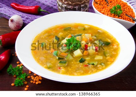 Healthy vegetable soup with red lentils, chili pepper and zucchini in a white ceramic plate - stock photo