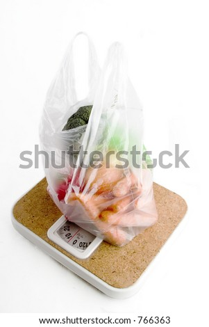Healthy vegetables in a clear plastic grocery bag on a scale - stock photo