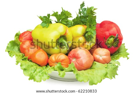 Healthy vegetables (peppers, tomato, lettuce, parsley) on a plate isolated over white.