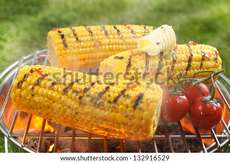 Healthy vegetarian barbecue with ripe golden corn on the cob and juicy red cherry tomatoes grilling over the fire outdoors on a green lawn - stock photo