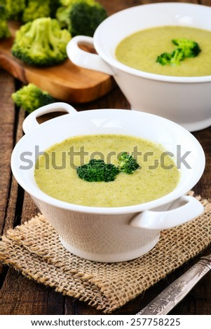 Healthy vegetarian cream of broccoli soup in white bowls on a rustic kitchen table