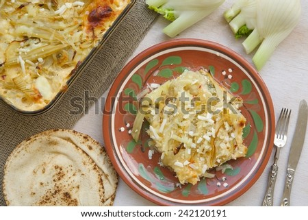 Healthy vegetarian dinner: oven baked fennel with potatoes and cheese. Glass mold with a dish , small Lebanese bread, fresh fennel bulbs,fork and a knife. Background. Top view.