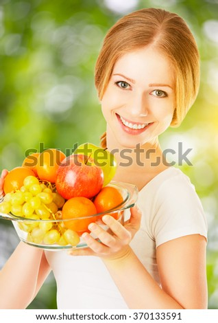 healthy vegetarian food. happy woman with a plate of fruit in the summer