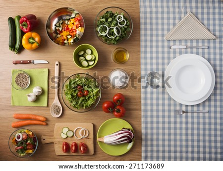 Healthy vegetarian meal concept with table set, fresh raw vegetables and dishware - stock photo
