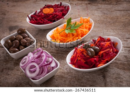 Healthy vegetarian salads variety with carrot, onion, beet and olive - stock photo