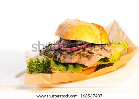 Healthy vegetarian seafood burger with a fillet of cold fish on lettuce and topped with onion on white background