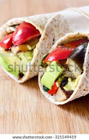 Healthy vegetarian vegan burrito wraps with roasted vegetables like aubergine eggplant, red bell peppers, avocado  - stock photo