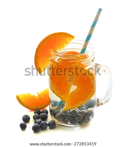 Healthy vitamin water with oranges and blueberries in a mason jar over a white background