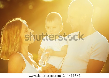 Healthy water concept. Happy family having fun. Baby boy with his mother and father posing together with plastic bottle of water. Outdoor shot - stock photo