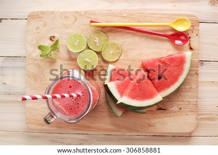 Healthy watermelon lime smoothie and fresh watermelon on wooden background - stock photo