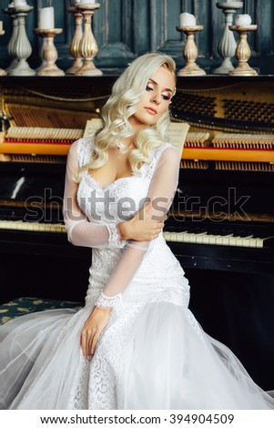 Healthy wedding hair. Gorgeous bride with long blonde curly hairstyle and bridal makeup on background of piano. Beauty indoor portrait. Attractive woman looking away - stock photo