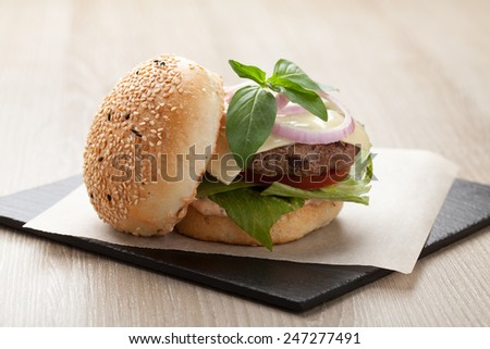 Healthy wheat sandwich burger with beef steak, cheese, tomato, lettuce, onion, basil and ketchup  served for eating - stock photo