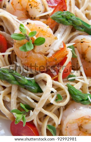 Healthy whole grain linguine with shrimps, asparagus, cherry tomatoes, fresh Parmesan cheese, and  oregano. - stock photo
