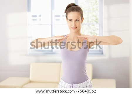 Healthy woman doing morning exercise in bright living room, smiling.?