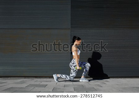 Healthy woman doing strength training with dumbbells against black line background outdoors, athletic female lifting weights while working out against wall with copy space for your text message - stock photo