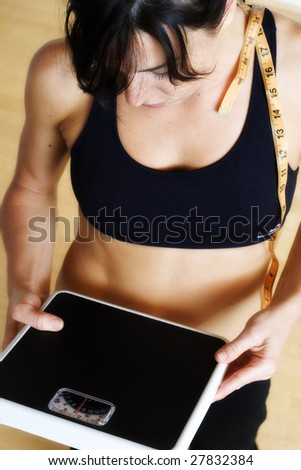 healthy woman looks at the scale