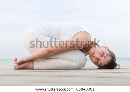 Healthy woman resting and curl up in fetal position outdoor at sea: yoga pose. - stock photo
