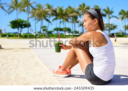 Healthy woman runner drinking green vegetable smoothie resting and relaxing after running.  Fitness and healthy lifestyle concept with multicultural Asian Caucasian female model. - stock photo