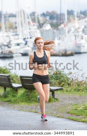 Healthy woman running near water outside - stock photo