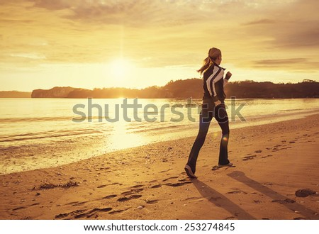 Healthy woman running on the beach at sunset - stock photo
