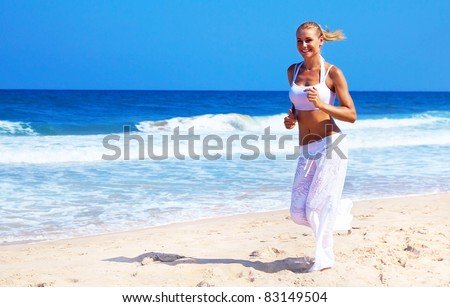 Healthy woman running on the beach, doing sport outdoor, freedom, vacation, heath care concept with copy space over natural background - stock photo