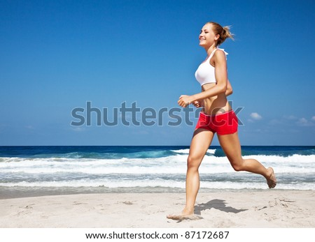 Healthy woman running on the beach, doing sport outdoor, freedom, vacation, heath care concept with copy space over natural blue background - stock photo