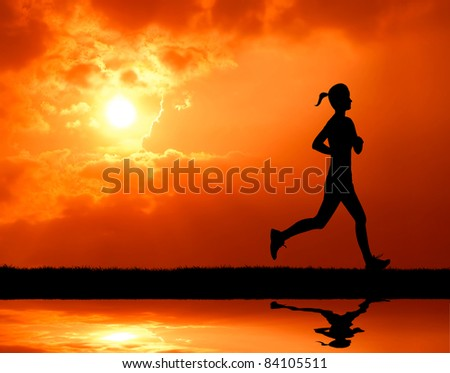 healthy woman running past the sun at sunset silhouetted - stock photo