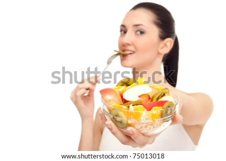 healthy woman showing healthy food, bowl with fruit salad in focus, isolated - stock photo
