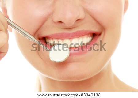 Healthy woman teeth and a dentist mouth mirror isolated over white