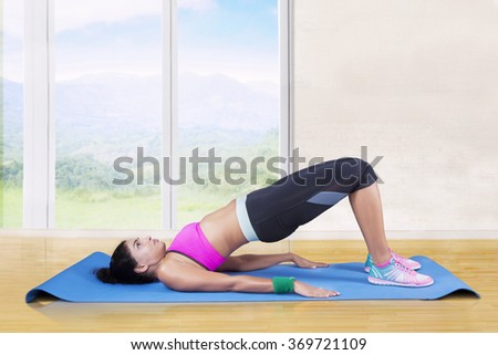 Healthy woman wearing sportswear and doing yoga workout at home while practicing the bridge pose - stock photo