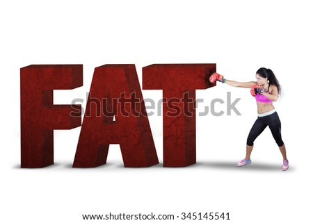 Healthy woman wearing two boxing gloves to punch a text of fat in the studio, isolated on white - stock photo