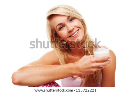Healthy woman with a radiant smile full of vitality holding a glass of milk isolated on white