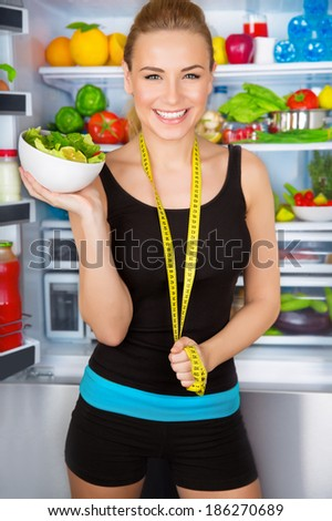 Healthy woman with fresh salad standing near open fridge full of vegetables, athletic girl with measure tape, perfect body, organic food concept
