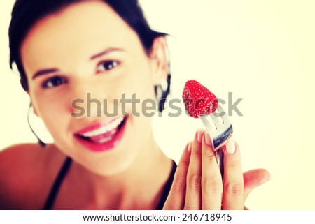 Healthy woman with strawberry on fork.   - stock photo