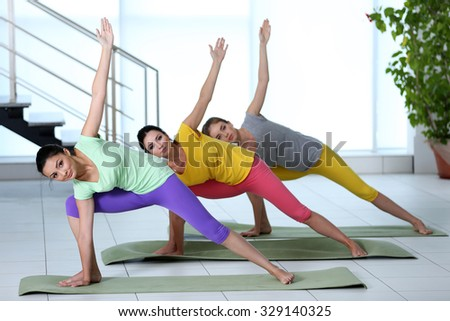 Healthy women do yoga exercises in a gym