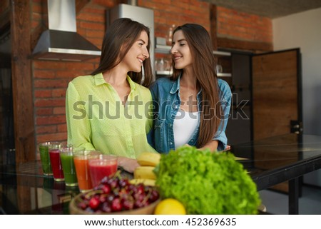Healthy Women Having Fun Together In Kitchen. Closeup Of Beautiful Happy Smiling Fit Girls Standing At Table With Glasses Of Fresh Juice, Detox Smoothie, Fruits And Vegetables On It. Diet Nutrition