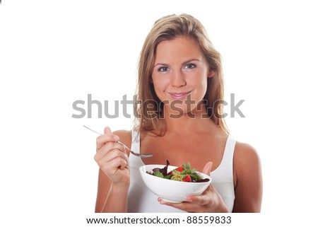 Healthy women in a white tank top eats a fresh green salad with fruit - stock photo