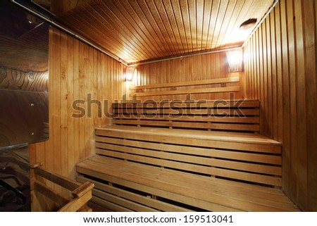 Healthy wooden steam sauna with with two lamps and wood seating - stock photo