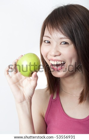 healthy young asian smiling with a green apply - stock photo