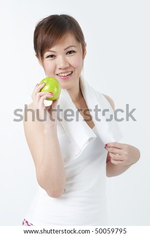 healthy young asian with an apple after exercise - stock photo