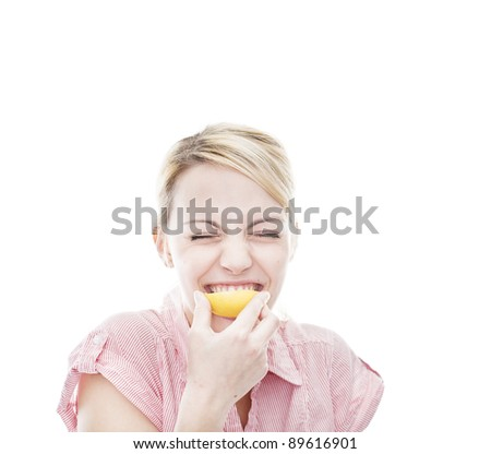 healthy young blonde attractive woman bites in a lemon and makes a face