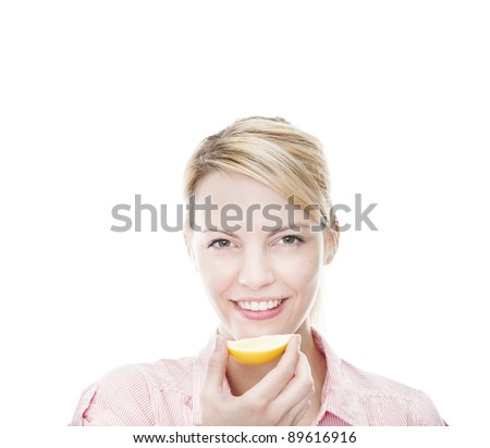 healthy young blonde woman holds a sliced lemon and smiles