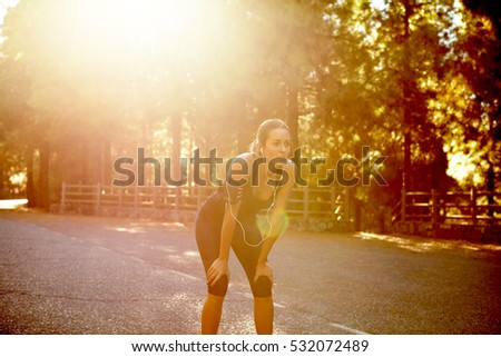 Healthy young brunette woman catching her breath alone on a tarred road surrounded with a forest of trees in the glare of the sun