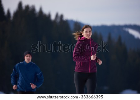 healthy young couple jogging outside on snow in forest. athlete running on  beautiful sunny winter day - stock photo