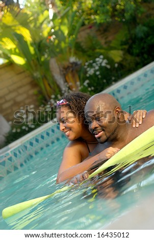 Healthy young couple swimming together in the pool - stock photo