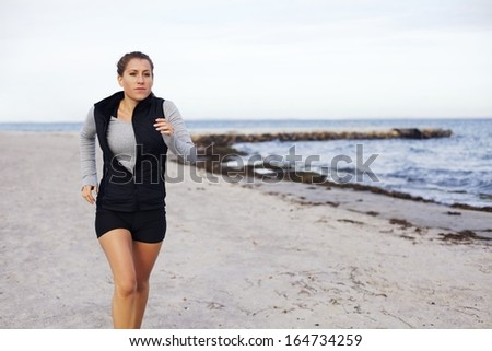 Healthy young female jogging on seashore. Beautiful caucasian woman athlete running and exercising on the beach with copyspace - Outdoors - stock photo