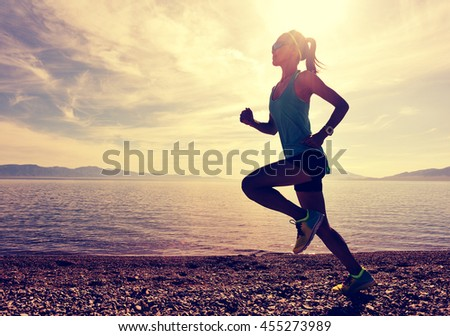 healthy young fitness woman runner running on sunrise seaside - stock photo
