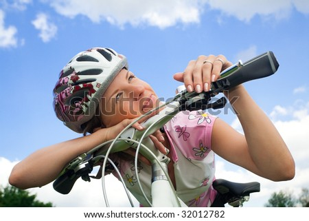 Healthy young girl with bicycle looking at the sun