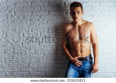 Healthy young guy posing near a white brick wall.