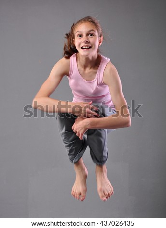 Healthy young happy smiling teenage girl dancer skipping jumping and dancing in grey studio. Child exercising. Sport healthy lifestyle concept. Sporty childhood. Isolated over grey background. - stock photo